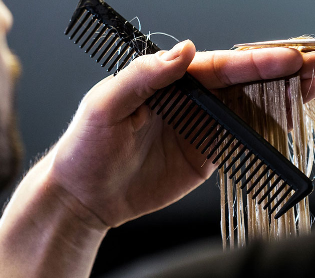 Close up of hairstylist holding hair with comb