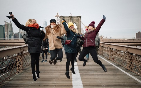group of ladies jumping on the brooklyn bridge