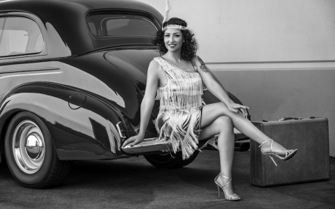 black and white photo of flapper sitting on the back of a retro car