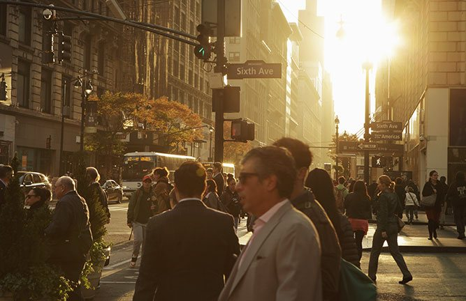 Crowd of people walking on the streets of New York as the sun sets