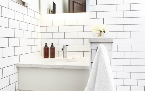 Full bathroom with white marble countertops & white tile walls