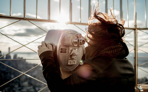 Woman looking through binoculars at the top of building overlooking the city