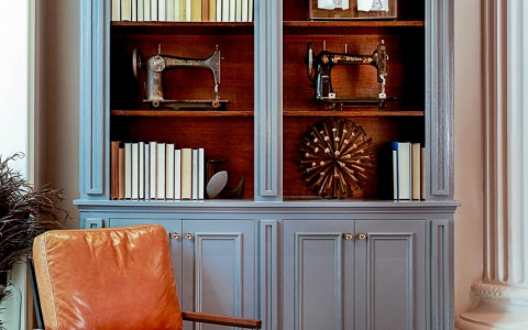 Leather chair in front of grey wooden book shelf with antique sewing machines
