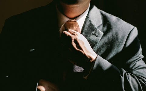 Close up of man fixing tie