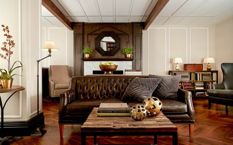 Room with leather couch, wooden table & mirror with book shelf in the back