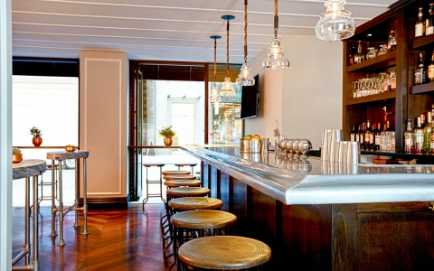 Wooden bar with marble countertop, wooden shelves & stools