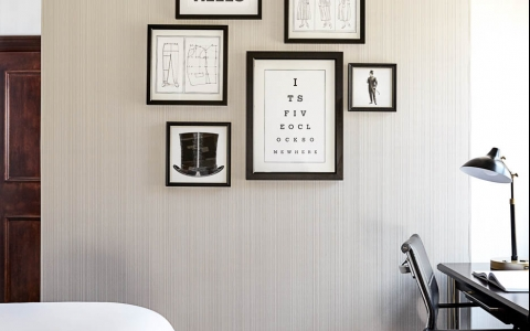 Different sized black frames with minimalistic art on wall next to desk