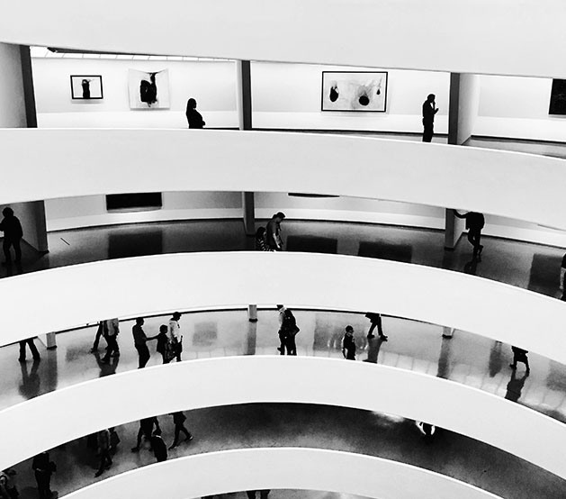 Black & white image of people walking through multiple floored museum