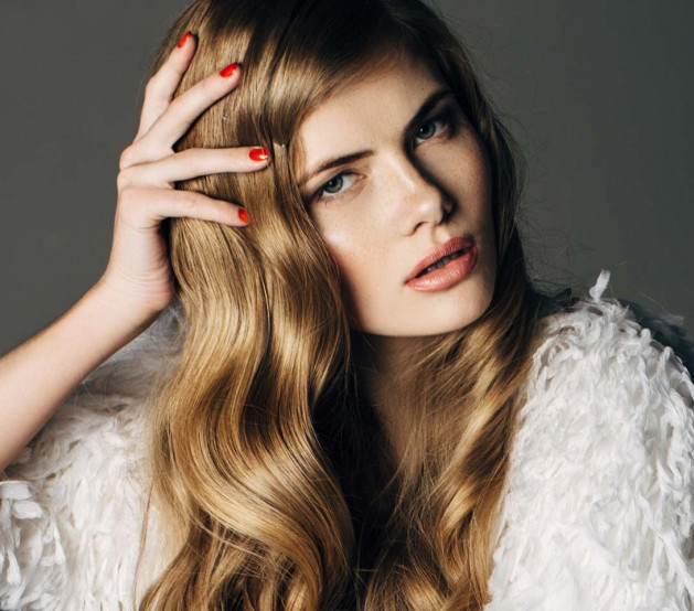 woman with red nail polish posing for a picture with her hair with waves