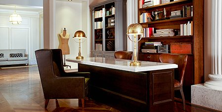 Room with wooden desk, leather chairs & book shelves