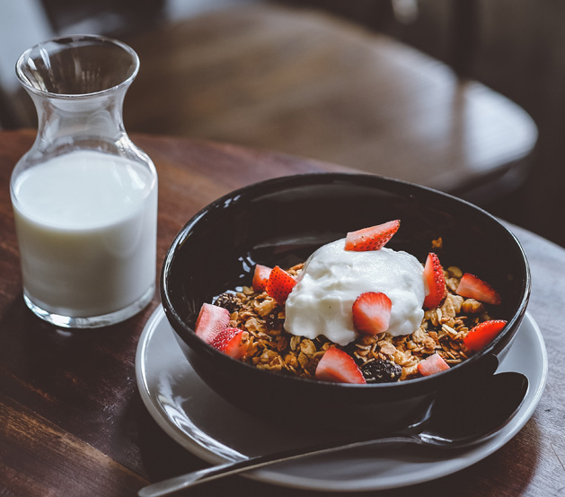 Bowl with granola & fresh fruits next to bottle of milk