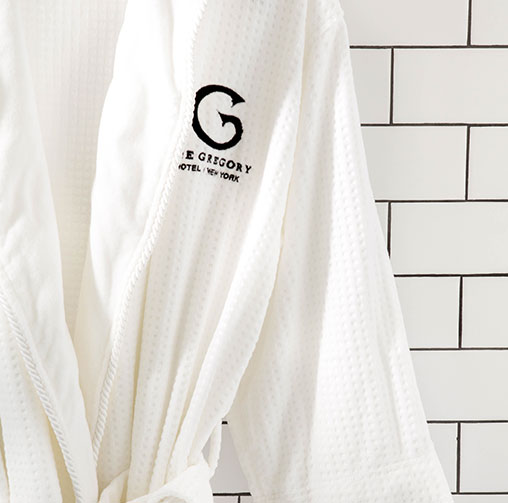 Close up of white bath robe with Gregory logo