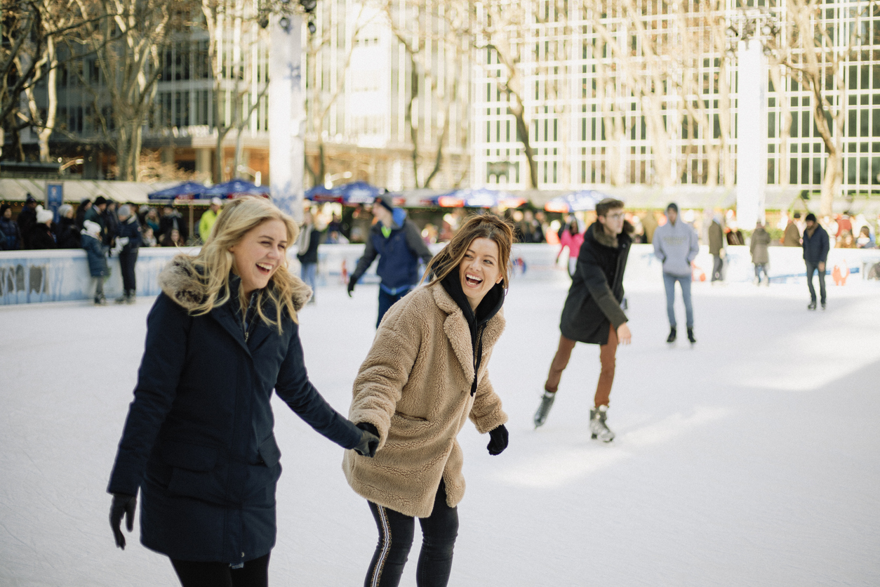 two women ice skating in new york city