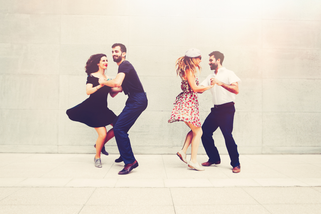 two couples swing dancing in summer clothes