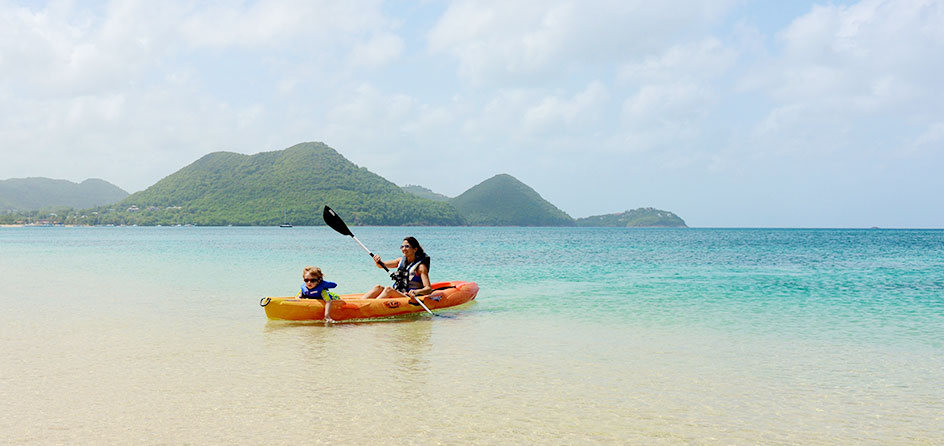 People kayaking in the ocean with island in background