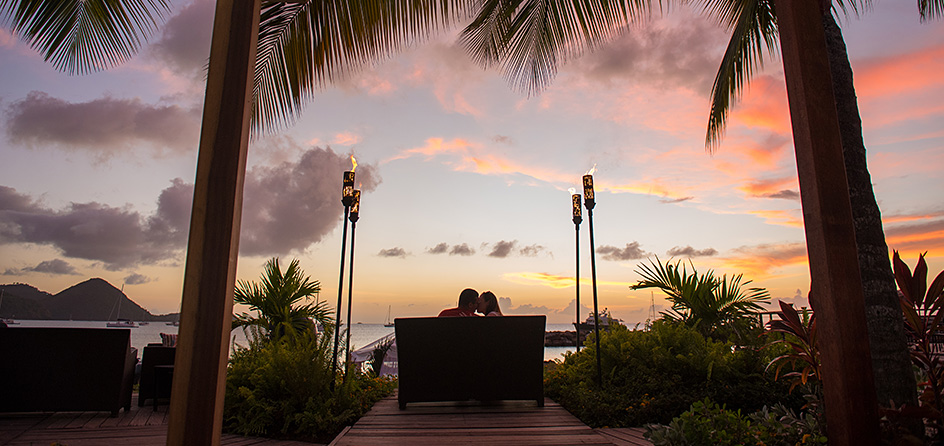 man and woman sitting together watching the sunset with an ocean view