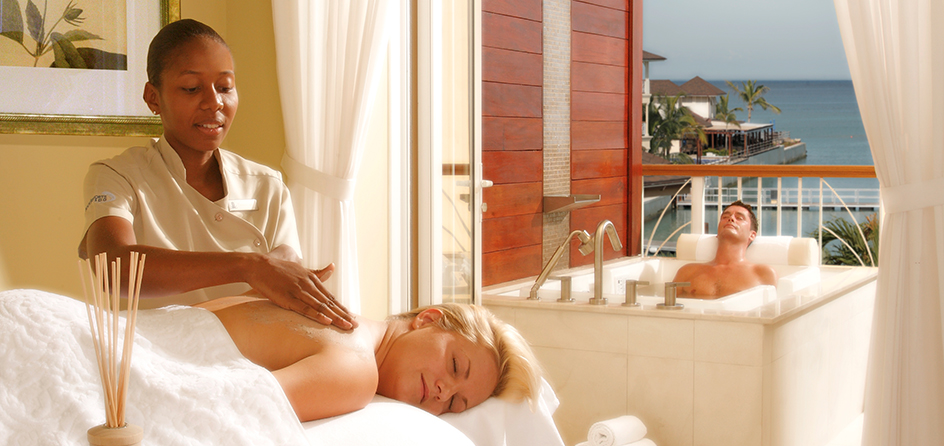 woman getting a back massage while a man sits in a tub behind her and the ocean is in the background