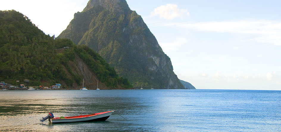 small boat on the water with island mountains in the background