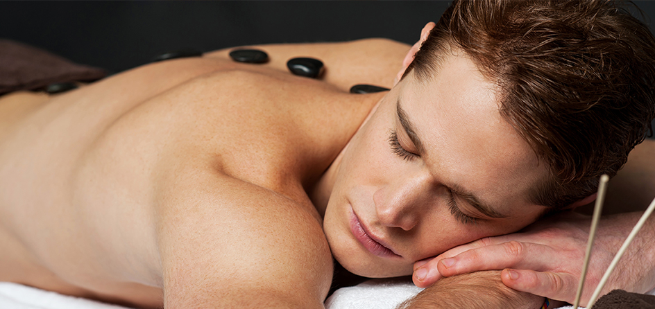 man laying down with hot stones on his back