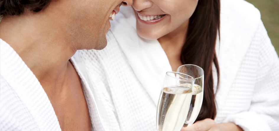 man and woman in robes smiling at each other and holding champagne