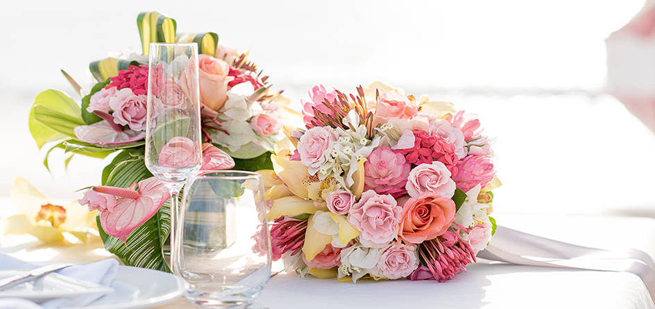 bouquets of flowers on a white table next to drink glasses