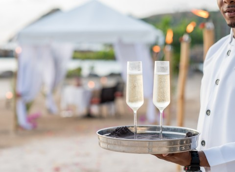 waiter holding a tray with champagne glasses and beach cabana in background