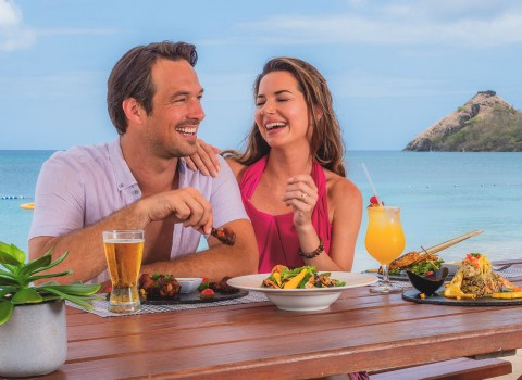 Couple laughing during dinner on the beach