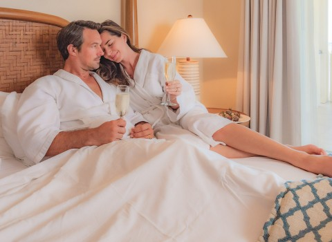 Couple laying in bed with champagne