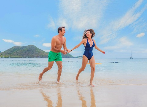 man and woman running hand in hand on the beach