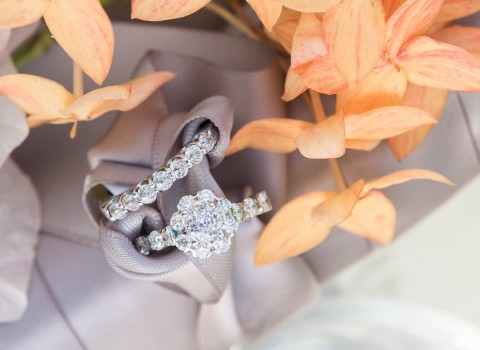 close up of a brides engagement ring and wedding band close to orange flowers