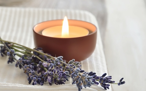 candle burning near purple flowers