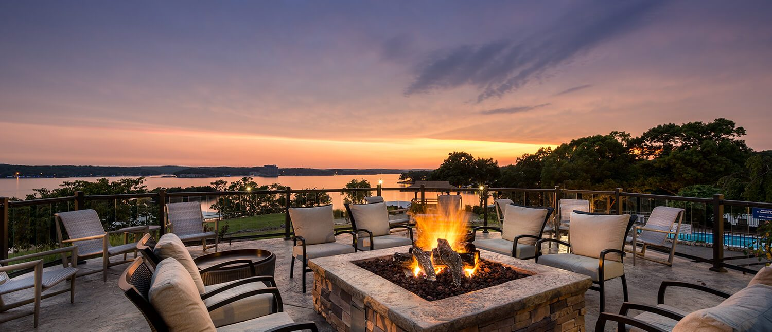 Fire pit with chairs around it and water in the background at sunset