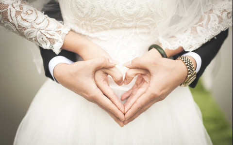 midsection of bride and groom making a heart shape with their hands