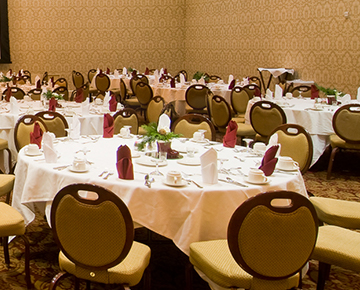 hotel meeting space filled with round tables and chairs