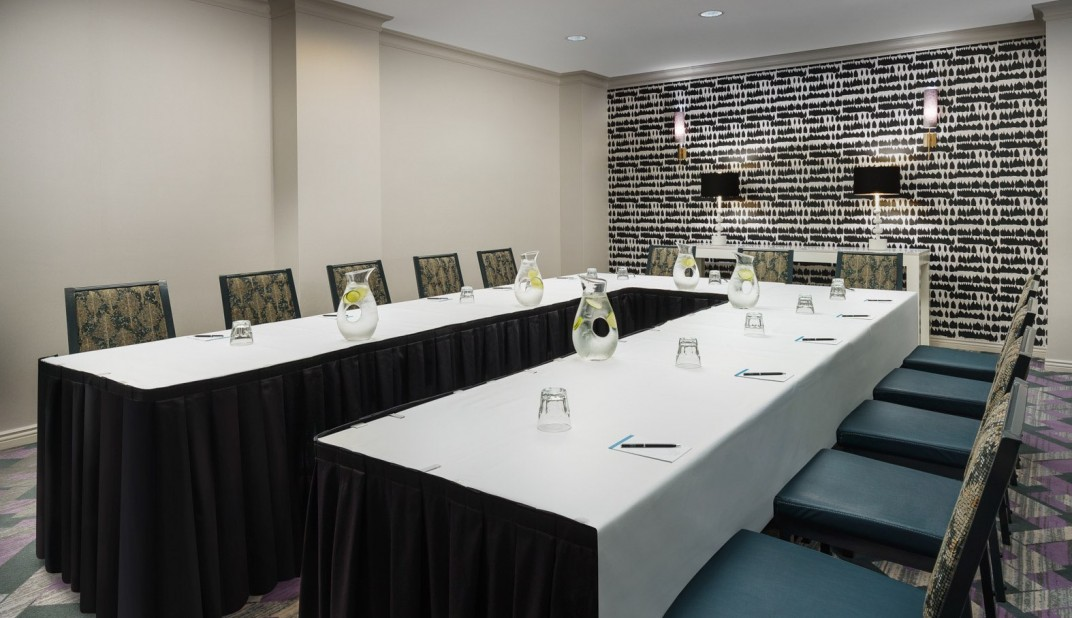 marker hotel meeting room with conference tables set up in a U shape