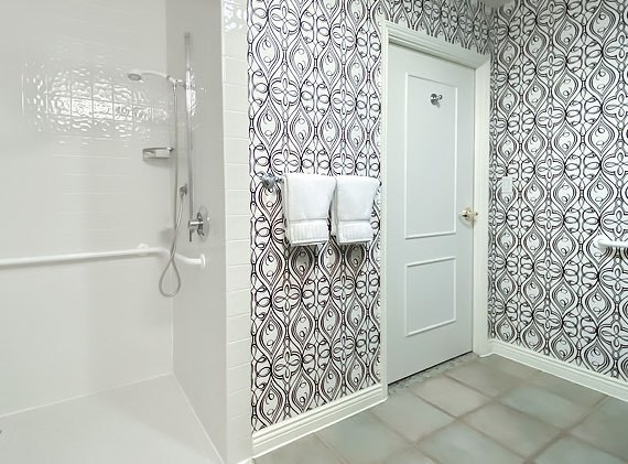 walk in accessible shower in bathroom with black and white printed walls