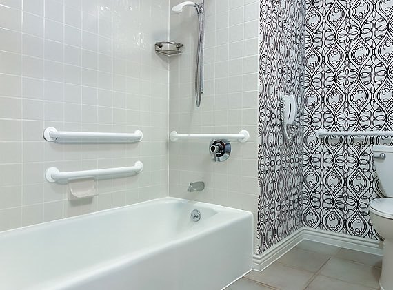 white tub in bathroom with black and white printed wall