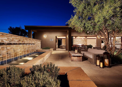 Outdoor terrace at night with a stone waterfall, large tree decorated with lights, and couch and chair seating areas