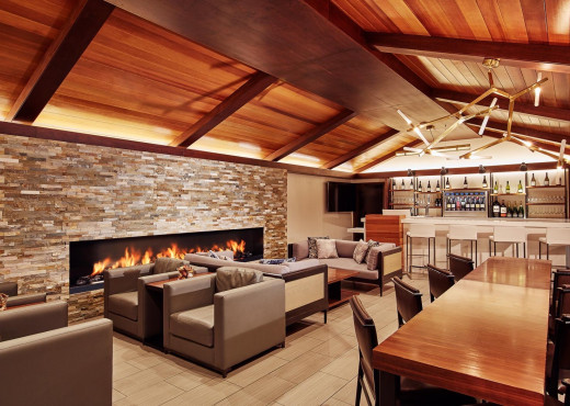 Interior of a lounge and bar seating area with wooden ceilings, couches and chairs around a stone fireplace and various wines displayed behind the bar counter