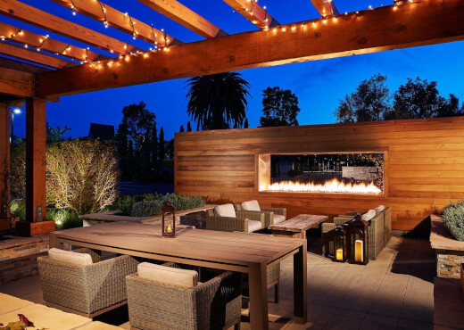 Outdoor fireplace area at night with cushioned chair seating, rustic wood coffee table, wooden patio table, and string lights hanging around a wooden gazebo