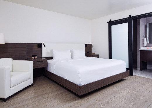King bedroom with white sheets and a dark wood built in frame, wide cushion chair and lamp, built in nightstands, and a sliding opaque barn door leading to the bathroom
