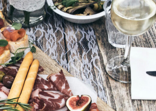 A nicely decorated charcuterie board and a glass of white wine on a wooden dining table