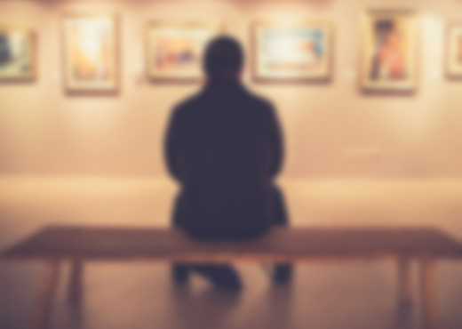 man on bench in art gallery