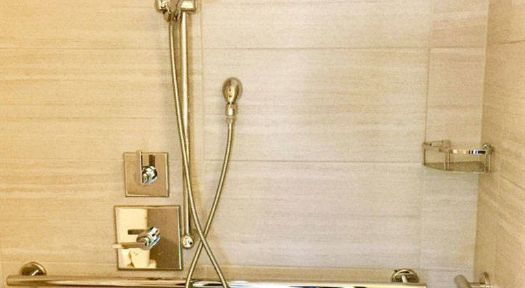 walk in shower with gold accents