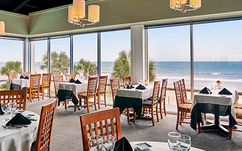 Dining room with table and chairs with large windows with an ocean view