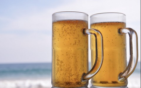 two beers mugs on the beach