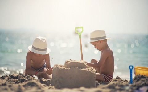 two boys building a sand castle