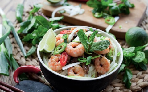 shrimp and vegetable bowl with cutting board in the back