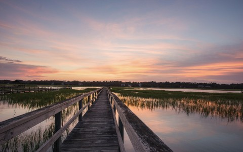 photo of a long lake dock at sunset