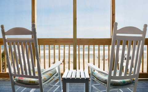 two chairs on balcony overlooking the beach
